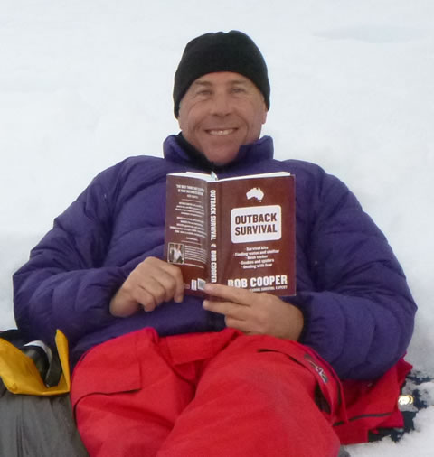 Chris Pervan in Antarctica with his copy of Outback Survival